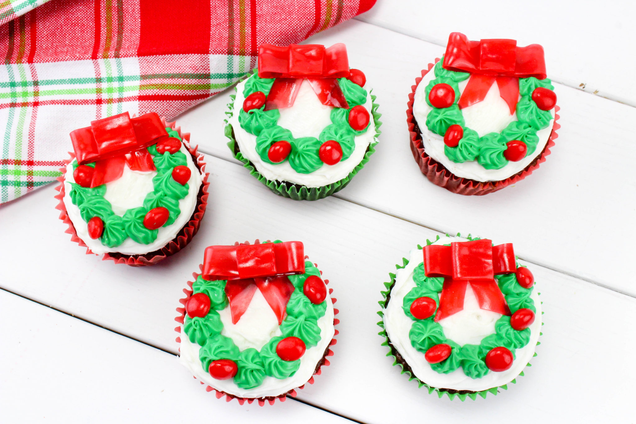 If you need a festive treat for a holiday party or to send into your kids classroom this year, these Christmas Wreath Cupcakes are what you are looking for.